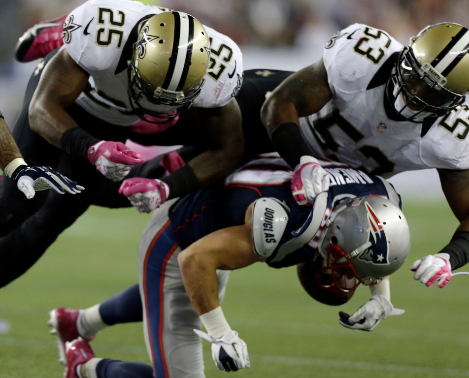 . New Orleans Saints defensive back Rafael Bush (25) and linebacker Ramon Humber (53) tackle New England Patriots wide receiver Danny Amendola after a catch in the third quarter of an NFL football game against the New Orleans Saints Sunday, Oct. 13, 2013, in Foxborough, Mass. Amendola was injured on the play. (AP Photo/Steven Senne)