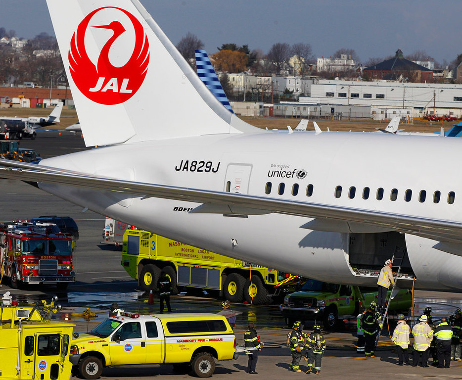 . A Japan Airlines Boeing 787 Dreamliner jet aircraft is surrounded by emergency vehicles while parked at a terminal E gate at Logan International Airport in Boston as a fire chief looks into the cargo hold Monday, Jan. 7, 2013. A small electrical fire filled the cabin of the JAL aircraft with smoke Monday morning about 15 minutes after it landed in Boston. (AP Photo/Stephan Savoia)