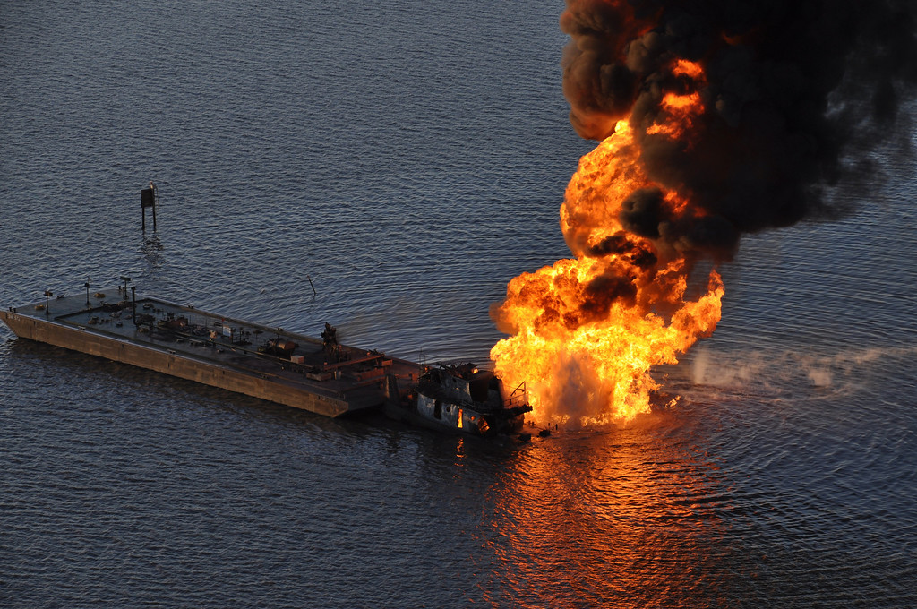. This US Coast Guard handout image shows a natural gas pipeline burning after a collision with the tugboat Shanon E. Setton near Bayou Perot 30 miles south of New Orleans, Louisiana March 13, 2012. The tug, pushing a barge loaded with crude oil struck a natural gas line, causing the fire, injuring at least two persons. The Coast Guard is working with federal, state and local agencies in response to this incident to ensure the safety of responders and contain and clean up any oil that is leaking.   AFP PHOTO / US Coast Guard Air Station New Orleans
