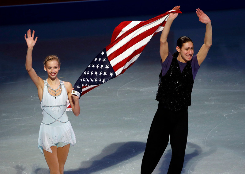 . U.S. Olympic figure skaters Polina Edmunds and Jason Brown carry a flag and wave to the crowd at the end of their skating spectacular after the U.S. Figure Skating Championships in Boston, Sunday, Jan. 12, 2014. (AP Photo/Elise Amendola)