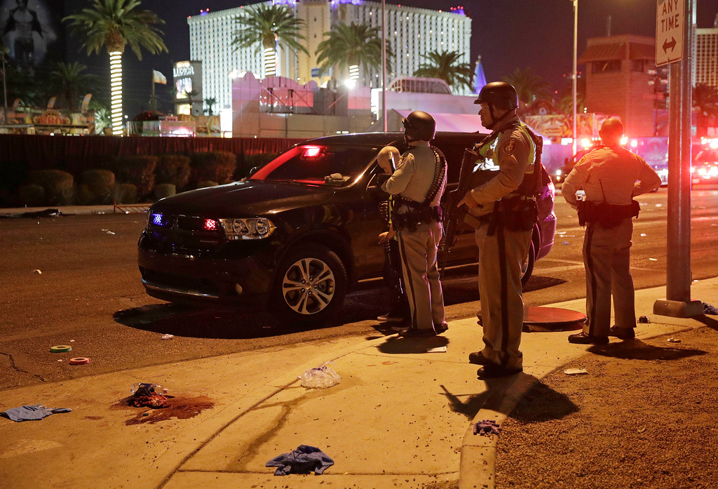 . Police stand at the scene of a shooting along the Las Vegas Strip, Monday, Oct. 2, 2017, in Las Vegas. Multiple victims were being transported to hospitals after a shooting late Sunday at a music festival on the Las Vegas Strip. (AP Photo/John Locher)