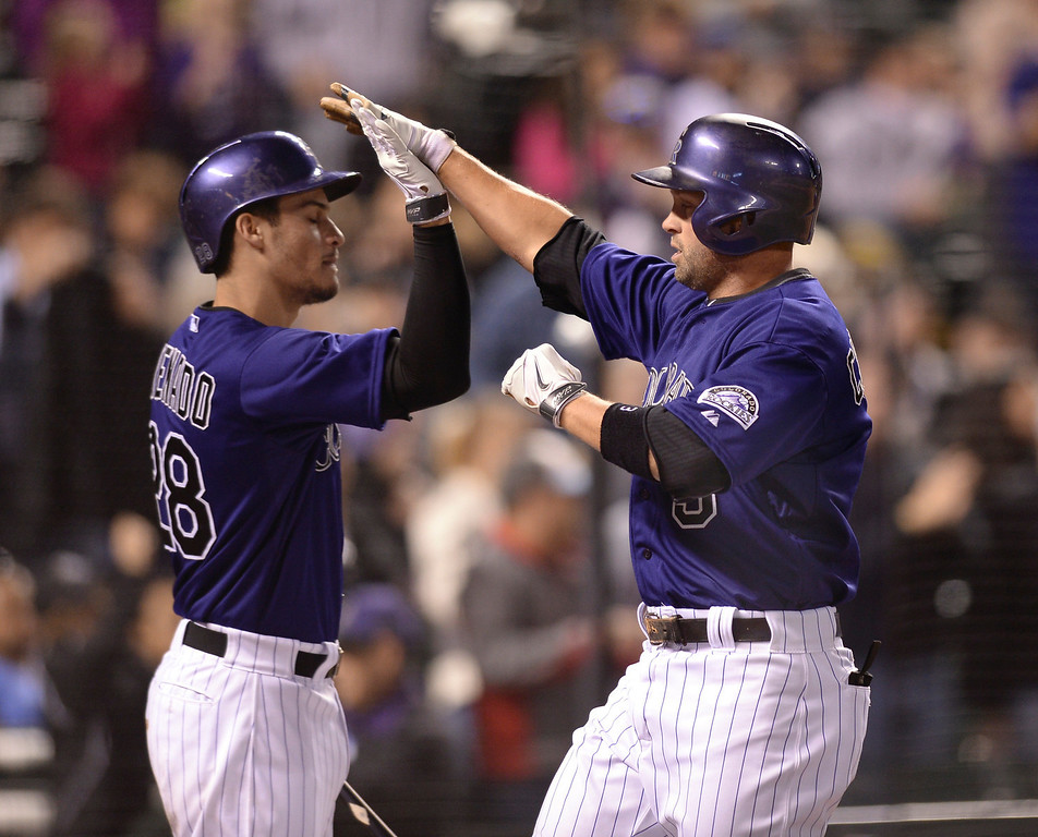. Michael Cuddyer, right, slapped hands with Nolan Arenada, left, as he came back to the dugout after hitting a home run in the fourth inning.  (Photo by Karl Gehring/The Denver Post)