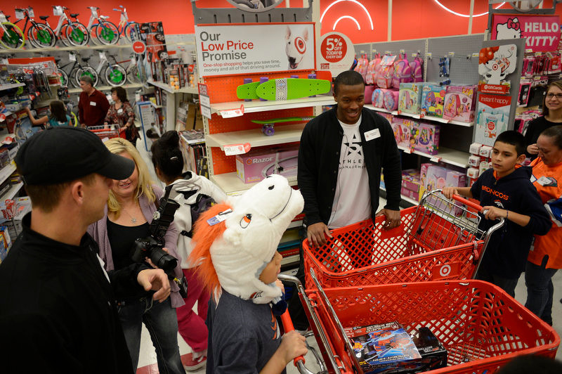 . Broncos Demaryius Thomas (R) and Brandon Stokely (L) shops with kids during their shopping spree at TArget. Broncos wide receivers Eric Decker and Demaryius Thomas along with other teammates reached out to help children in their community by hosting a holiday shopping trip at Super Target Tuesday, December 11, 2012 in Lone Tree. 25 children, ranging in age from 8 to 14, are being rewarded for their outstanding participation in their after-school program with a trip to buy holiday presents. John Leyba, The Denver Post