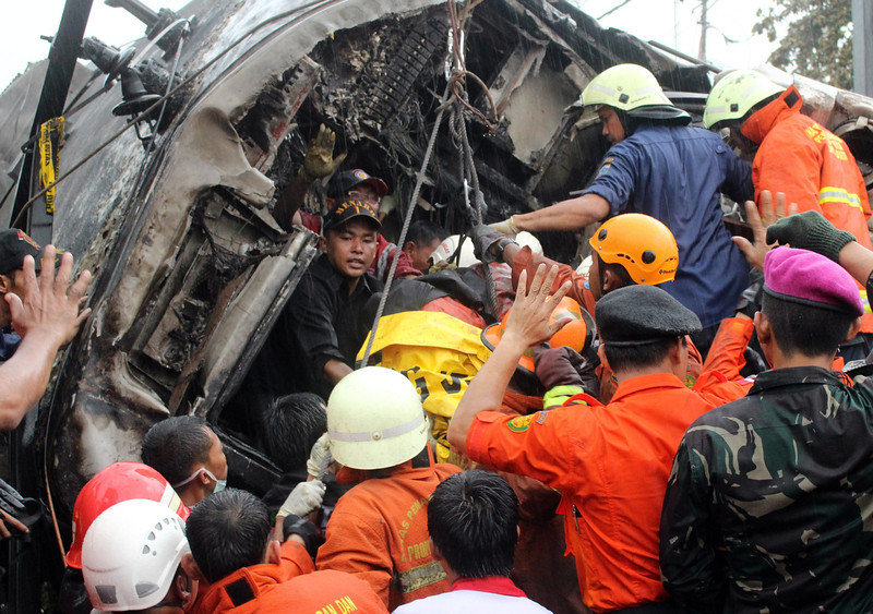 . Emergency rescuers evacuate bodies of victims from a collided commuter train in Jakarta, Indonesia, 09 December 2013. A commuter train ploughed into a truck carrying petrol in the Indonesian capital Jakarta, killing at least seven people and injuring more than 60, police said. The crash at a level crossing in south Jakarta sparked an explosion and sent a column of fire into the sky, television footage showed.  EPA/ADI WEDA