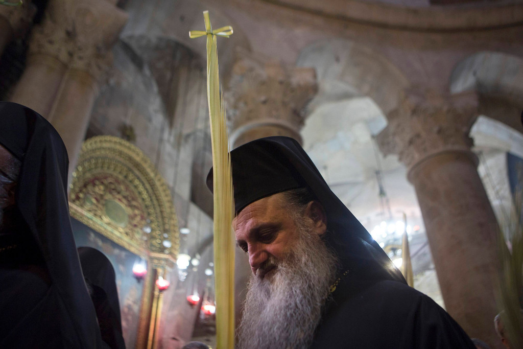 . A Greek Orthodox priest holds a palm frond during the Orthodox Palm Sunday mass in the Church of the Holy Sepulchre in Jerusalem\'s Old City April 28, 2013. REUTERS/Baz Ratner