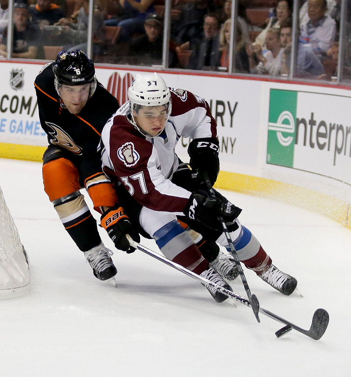. Anaheim Ducks defenseman Ben Lovejoy, left, battles Colorado Avalanche center Colin Smith for the puck during the first period of an NHL hockey preseason game in Anaheim, Calif., Monday, Sept. 22, 2014. (AP Photo/Chris Carlson)