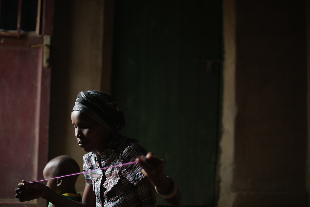 ". Jaqueline Mukamana weaves a thread and grass basket in her home in a genocide ""reconciliation village\"" April 6, 2014 in Mybo, Rwanda. Jaqueline\'s five sisters, two brothers and four uncles were killed during the 1994 genocide and she was left destitute. She was offered a home in Mbyo if she agreed to live near people who had commited the killing. At first she was apprehensive but when her new neighbors offered to help her recover her family\'s remains she was able to forgive them. Organized by the Prison Fellowship Rwanda in 2004, this village of 285 is where those who served time in prison for genocide now live side-by-side with people who survived the killer\'s 1994 rampage. One of five communities like this in Rwanda, Mbyo residents share agriculture and handicraft cooperatives and say that working together has helped with reconciliation, easing their apprehension and fostering new friendships. Rwanda is preparing to commemorate the 20th anniversary of the country\'s 1994 genocide, when more than 800,000 ethnic Tutsi and moderate Hutus were slaughtered over a 100 day period.  (Photo by Chip Somodevilla/Getty Images)"