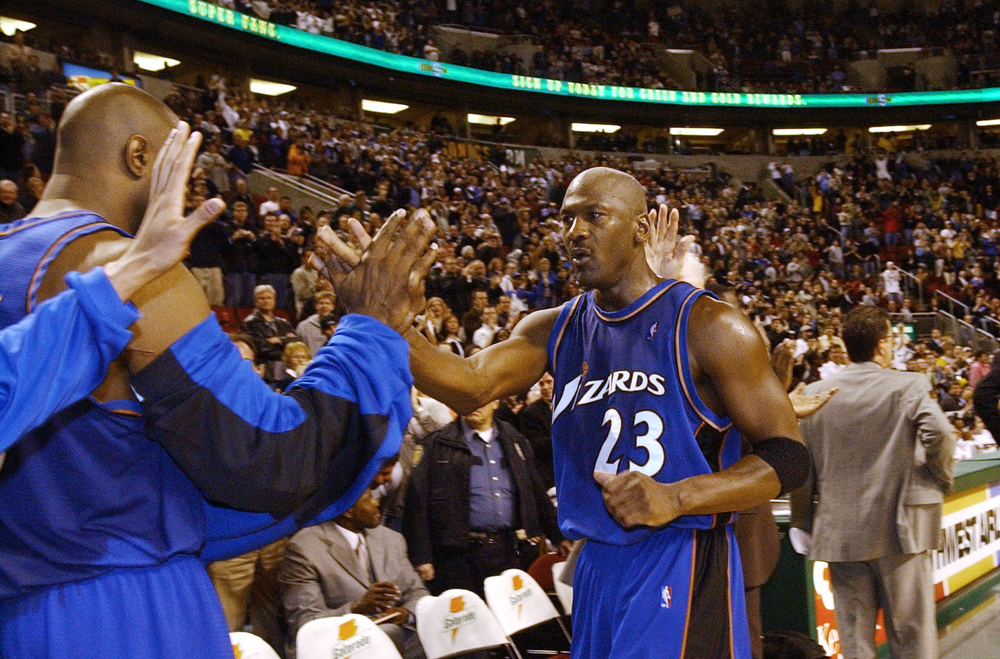 . Washington Wizards\' Michael Jordan (23) is congratulated by teammates as he leaves the game against the Seattle SuperSonics with seconds left Wednesday, March 26, 2003, in Seattle. Jordan led all scorers with 26 points in their 80-74 victory. The appearance was Jordan\'s last regular season game in Seattle. (AP Photo/Elaine Thompson)