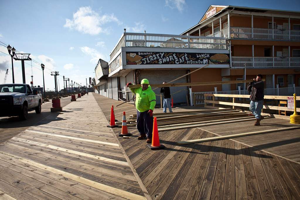 . Workers carry a wood plank as the Seaside Heights boardwalk and amusement park remains under construction one year after being partially destroyed by Superstorm Sandy in October 2012, and damaged again in September 2013 by an electrical fire, on October 29, 2013 in Seaside Heights, New Jersey.   (Photo by Kena Betancur/Getty Images)