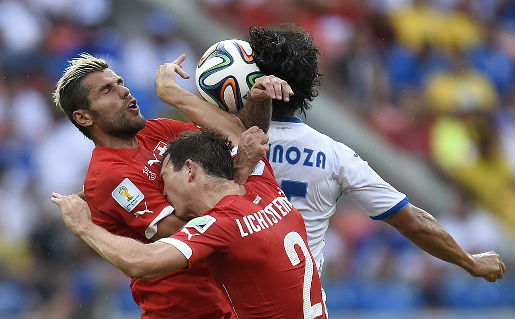 . Honduras\' midfielder Roger Espinoza (back) jumps to head the ball with Switzerland\'s midfielder Valon Behrami (L) and defender Stephan Lichtsteiner during the Group E football match between Honduras and Switzerland at the Amazonia Arena in Manaus during the 2014 FIFA World Cup on June 25, 2014. JUAN BARRETO/AFP/Getty Images