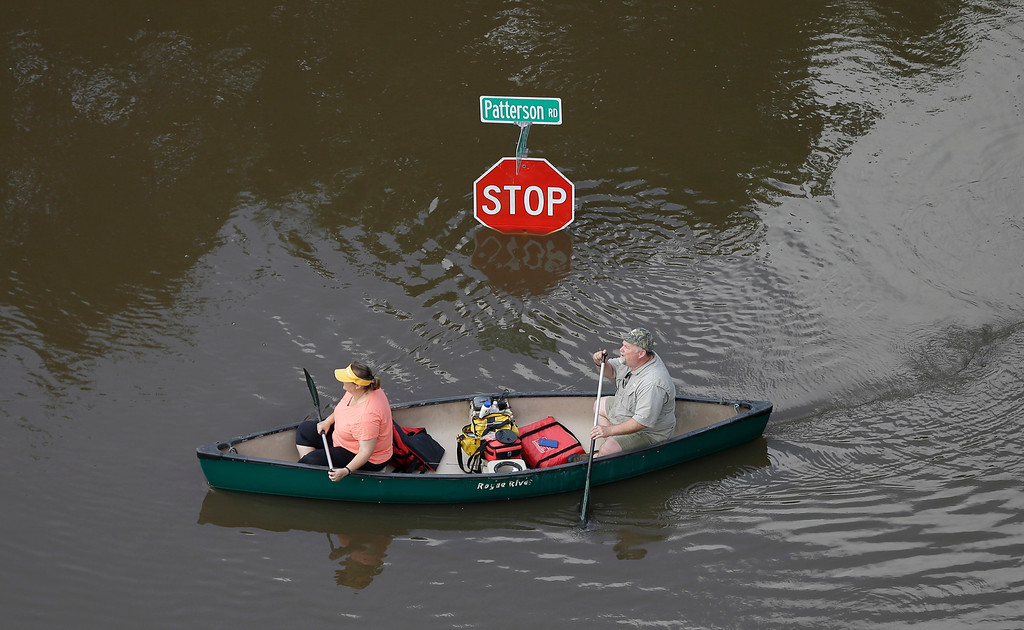 . In this aerial photo, people canoe through floodwaters past a stop sign near Bear Creek Park Saturday, May 30, 2015, in Houston. The Colorado River in Wharton and the Brazos and San Jacinto rivers near Houston are the main focus of concern as floodwaters move from North and Central Texas downstream toward the Gulf of Mexico. (AP Photo/David J. Phillip)