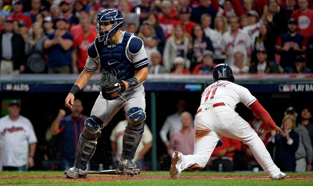 . Cleveland Indians\' Jose Ramirez, right, scores on a sacrifice fly by Jay Bruce as New York Yankees catcher Gary Sanchez waits for the ball in the fifth inning of Game 1 of a baseball American League Division Series, Thursday, Oct. 5, 2017, in Cleveland. (AP Photo/Phil Long)
