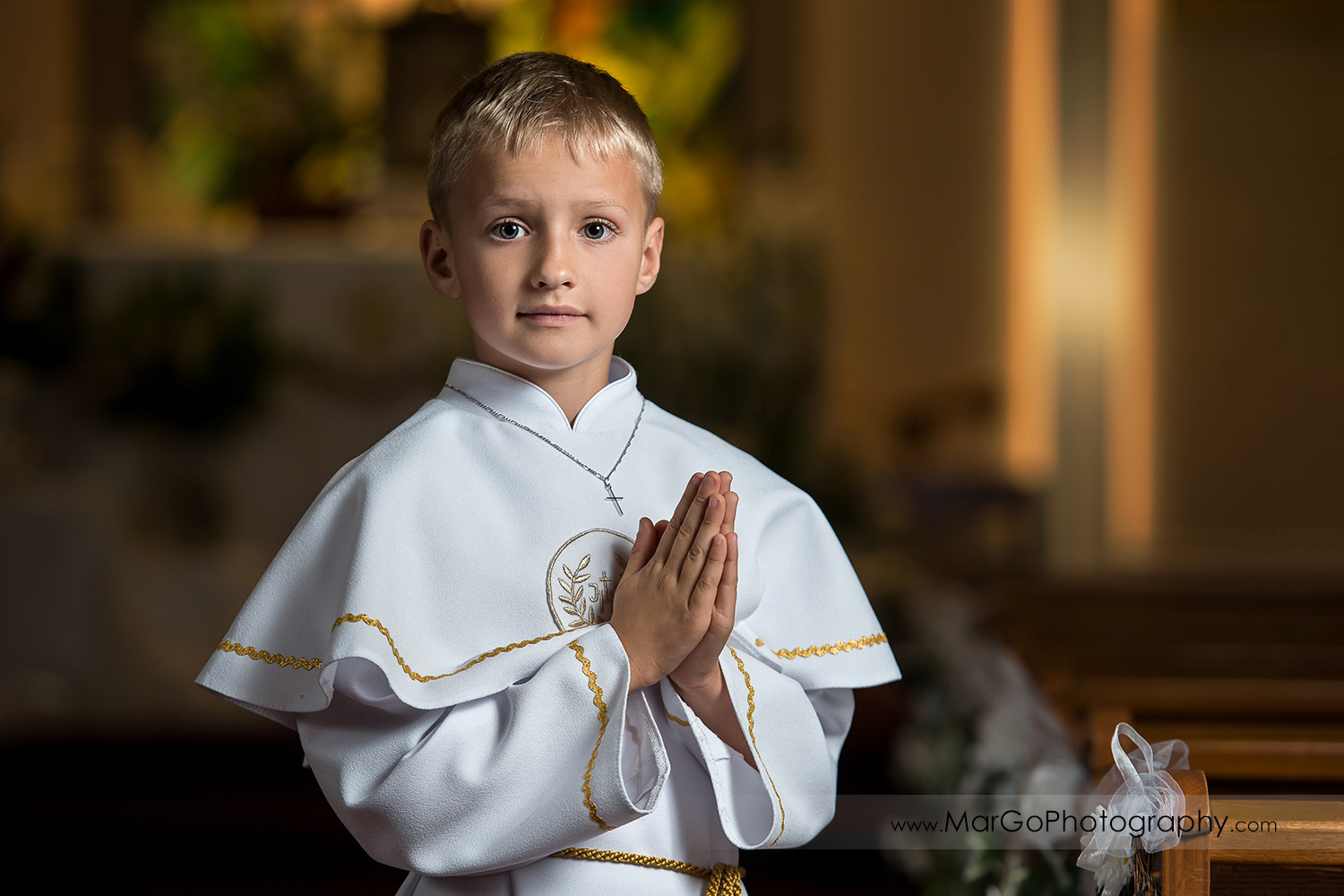first communion boy in white alb with folded hands standing in San Jose church middle aisle