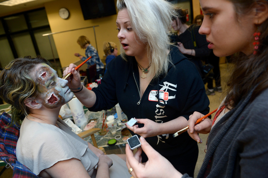 """. BOULDER, CO- FEBRUARY 19:  Danica Minor, middle, and Kristy Pike, right, both  make-up artists with Theatrical Costumes Etc, apply \""""Zombie\"""" make up to zombie Phillipa Keosheyan 14.  With the help of a professional videographer, Fairview High School students produced a zombie video to advertise an Awareness Drive in Boulder Valley schools designed to bring attention to a variety of mental health and wellness issues.  Students were made to look like zombies by make-up artists from Theatrical Costumes, Etc. (Photo By Helen H. Richardson/ The Denver Post)"""