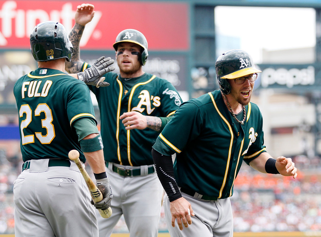 . Oakland Athletics\' Eric Sogard, right, and Brett Lawrie, center, celebrate with Sam Fuld (23) after scoring on a triple by Josh Phegley during the second inning of a baseball game against the Detroit Tigers at Comerica Park Thursday, June 4, 2015, in Detroit. The Athletics defeated the Tigers 7-5. (AP Photo/Duane Burleson)