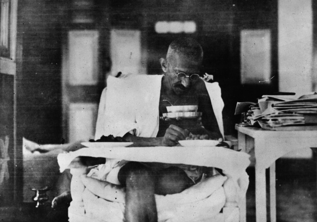 . Indian nationalist leader Mahatma Gandhi (Mohandas Karamchand Gandhi, 1869 - 1948) eating at his home, whilst living in seclusion after his release from prison by the British authorities, 1925.  (Photo by Topical Press Agency/Getty Images)