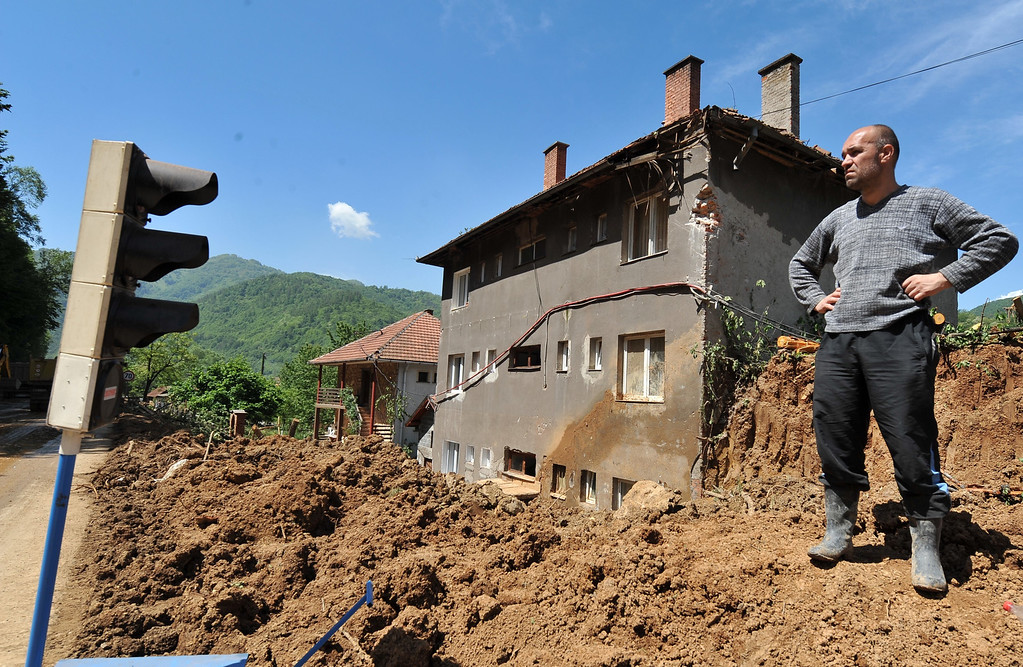 . A Bosnian man observes as workers use heavy machinery to clear earth from a landslide in the flooded village of Nemila in the municipality of Zenica, central Bosnia, on May 19, 2014, after the river Bosna flooded entire agricultural fields and several urban areas along its flow during the weekend\'s rainfall. Thousands crammed into boats and army trucks as they fled their homes in Serbia and Bosnia on MAy 18 after record rainfalls. Officials say the disaster has killed at least 44 people so far.  AFP PHOTO / ELVIS BARUKCIC/AFP/Getty Images