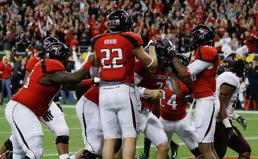 Description of . Seth Doege #7 of Texas Tech celebrates with his teammates after his a 4-yard touchdown in the second quarter against Minnesota during the Meineke Car Care of Texas Bowl at Reliant Stadium on December 28, 2012 in Houston, Texas.  (Photo by Scott Halleran/Getty Images)