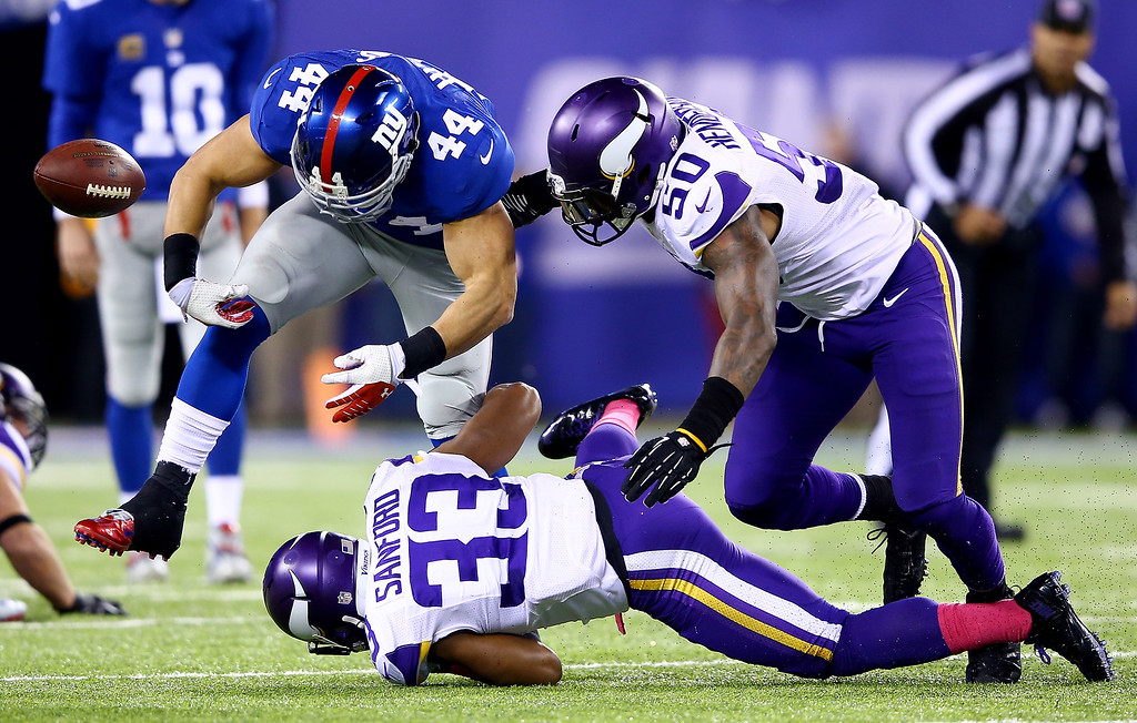 . Running back Peyton Hillis #44 of the New York Giants loses the ball as strong safety Jamarca Sanford #33 and middle linebacker Erin Henderson #50 of the Minnesota Vikings make the tackle during a game at MetLife Stadium on October 21, 2013 in East Rutherford, New Jersey.  (Photo by Al Bello/Getty Images)