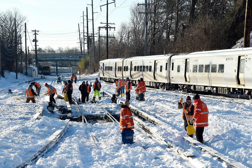 . Workers clear the tracks of snow at the Port Washington branch of the Long Island Railroad, Monday, Jan. 25, 2016, in Port Washington, N.Y.. Service is suspended on the Port Washington branch due to the recent snowstorm. (AP Photo/Kathy Kmonicek)