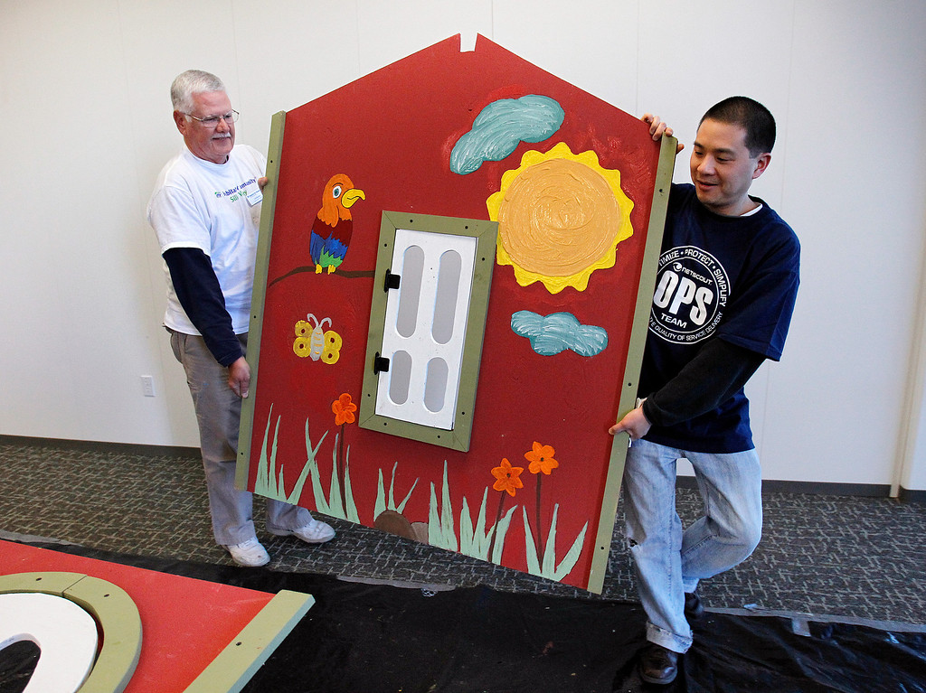 . From left, Habitat for Humanity Playhouse Program Head Ted Becker and NetScout Systems Service Desk Manager Andy Yuan move a finished playhouse wall at the NetScout offices in San Jose, Calif. on Thursday, Feb. 21, 2013.   (LiPo Ching/Staff)