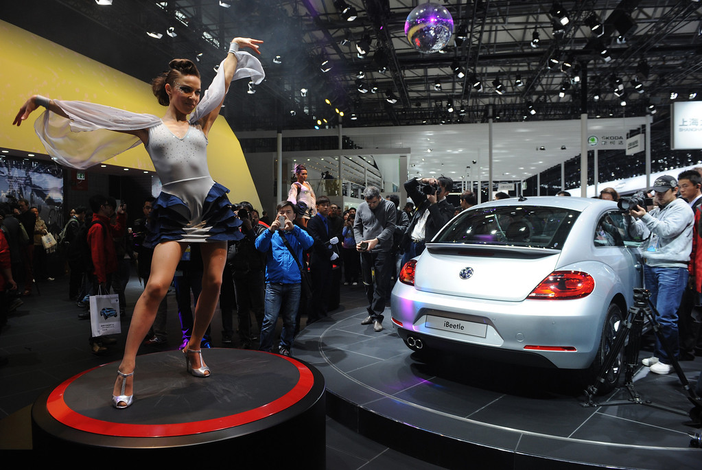 . This photo taken on April 20, 2013 shows a model dancing next to a VW Beetle (R) on media day at the Shanghai auto show. The Shanghai auto show, which opens to the public on April 21, is expected to attract more than 800,000 visitors over the course of nine days.   PETER PARKS/AFP/Getty Images