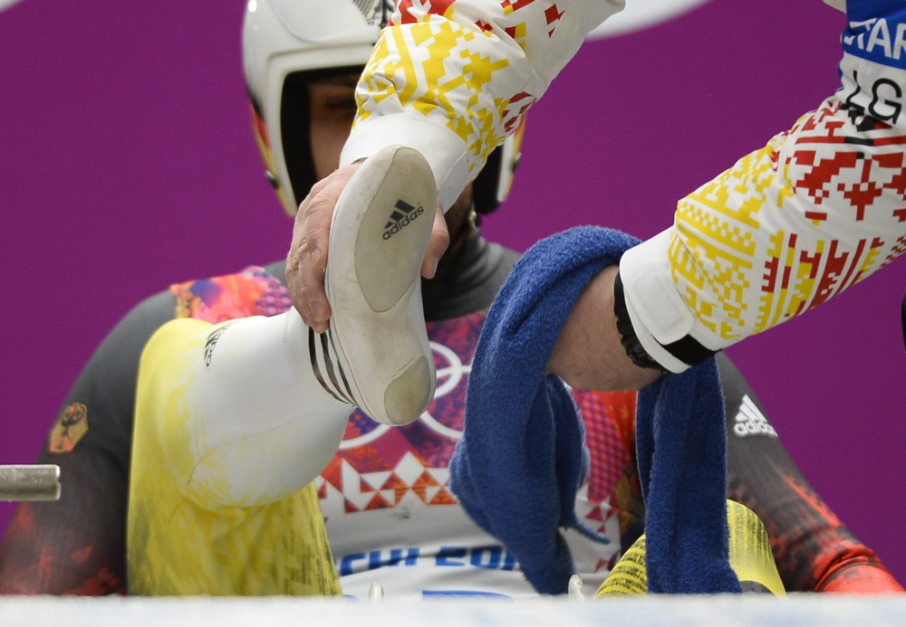 . A man wipes the feet of Germany\'s Andi Langenhan during the Men\'s Luge Singles run one at the Sliding Center Sanki during the Sochi Winter Olympics on February 8, 2014.  (LIONEL BONAVENTURE/AFP/Getty Images)
