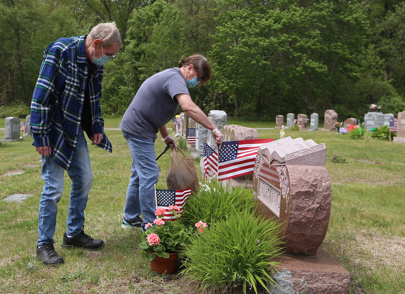Fox Hill Cemetery in Billerica, on Saturday of Memorial Day weekend. From left, Richard Bushong and his wife Jo Ann Bushong of Hudson, N.H., attend to the grave of Jo Ann's parents, Robert & Dorothy Fleming, one of a series of stops they were making at relatives' graves.  (SUN/Julia Malakie)