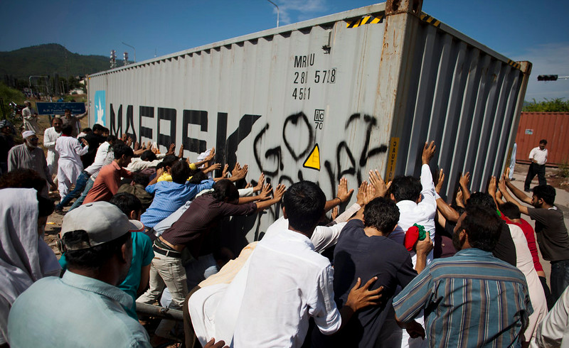 . Pakistani protesters push a container place by police to block protesters in Islamabad, Monday, Sept. 1, 2014. Anti-government protesters and Pakistani police have clashed once again as the demonstrators pushed into a sprawling government complex in the country\'s capital in an effort to try to reach the prime minister\'s official residence. (AP Photo/B.K. Bangash)