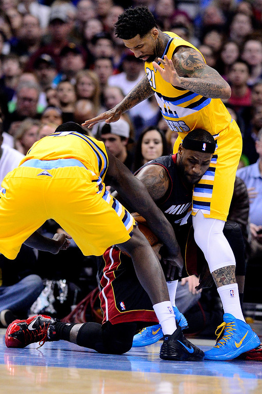 . LeBron James (6) of the Miami Heat goes down as he is defended by Wilson Chandler (21) of the Denver Nuggets and J.J. Hickson (7) of the Denver Nuggets during the first.   (Photo by AAron Ontiveroz/The Denver Post)