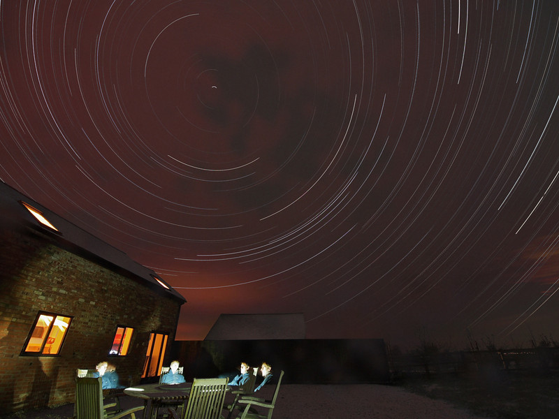 My third star trail shot with the Olympus E5. 26 Nov 2010. The only good thing about the unprecedented cold snap currently gripping the UK is the clear sky opportunities :-) For this shot I used the 7-14mm lens and  mounted the E5 on a tripod outside my house and composed around Polaris (around which the trail spins) and the table for which I added a bit of self portrait trickery :-) To do this I sat at each position for 30s and move to the next position. A torch was placed on the table for each pose. IS0 set to 400 opened the aperture as wide as it went (F4) and shot 15s exposures continuously all night from approx 7pm to 7am the next morning. Noise reduction was switched OFF. Camera was powered via external using extension lead from garage. To prevent the camera and lens from dewing and freezing over my home made dew shield was used. However, this did not prevent the snow from falling and covering the camera! As you can see from the clouds  in the trail snow rolled in early hours and the snow spots on the lens can just be seen bottom right of frame. Oh well! The following morning I retrieved the camera where temps dropped to -5C. The shutter release button was frozen solid with snow/ice. After downloading the 2500 images and running through stacking software the final composite, that you see, was produced.  The image was imported into Aperture with a tiny levels adjustment and removal of some annoying plane light trails. NO noise reduction filter was applied and reduced from the original JPEG size to this one you see with No sharpening.
