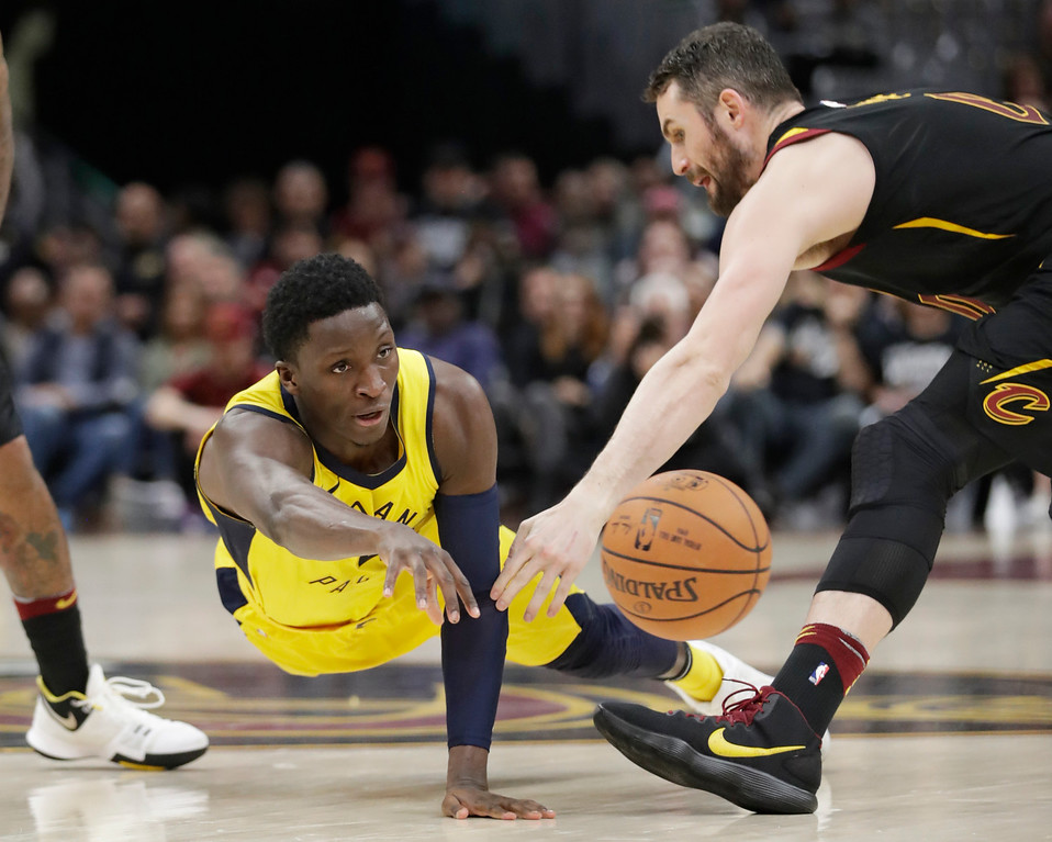 . Indiana Pacers\' Victor Oladipo, left, passes against Cleveland Cavaliers\' Kevin Love in the second half of Game 1 of an NBA basketball first-round playoff series, Sunday, April 15, 2018, in Cleveland.  (AP Photo/Tony Dejak)