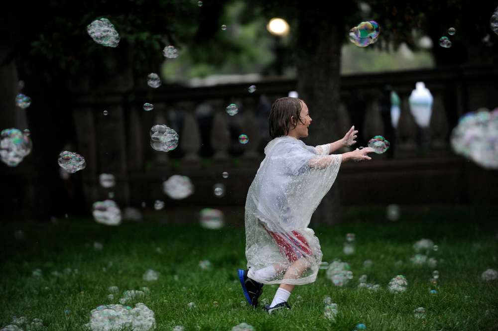 . Seth Vallejos, 8, plays in the bubbles as it rains during the 43rd annual People\'s Fair in Civic Center Park in Denver, Colorado on June 8, 2014. (Photo by Seth McConnell/The Denver Post)