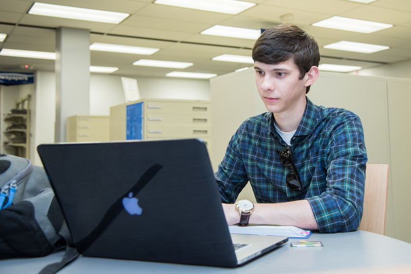 Student Sam Beattie studies in the Mary and Jeff Bell Library for his online economics course online.