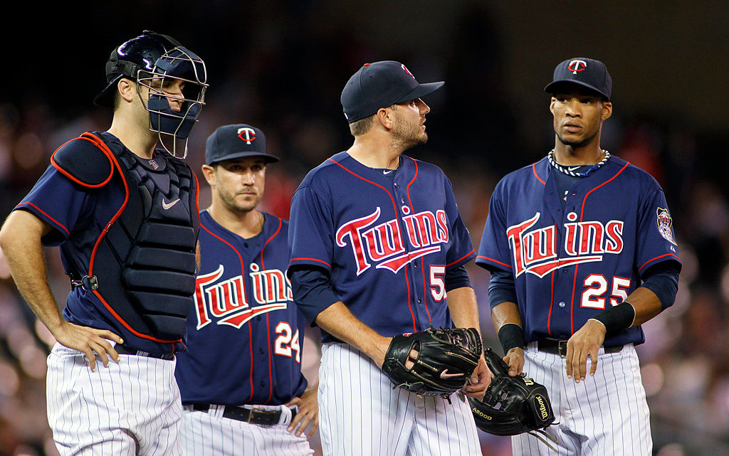 . Minnesota Twins players, left to right, Joe Mauer, Trevor Plouffe and Pedro Florimon wait for pitcher Brian Duensing to be pulled in the ninth inning. (AP Photo/Andy King)