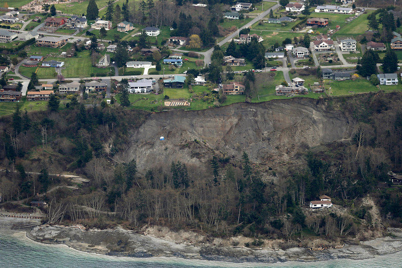 . An aerial photo shows a landslide near Coupeville, Wash. on Whidbey Island, Wednesday, March 27, 2013. The slide severely damaged one home and isolated or threatened more than 30 on the island, about 50 miles north of Seattle in Puget Sound. No one was reported injured in the slide, which happened at about 4 a.m. Wednesday. (AP Photo/Ted S. Warren)