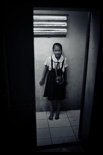 Girl standing behind the door.