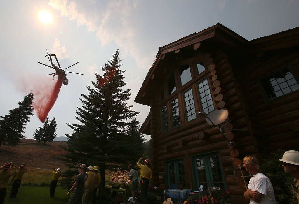 . A helicopter makes a drop on a dozer line around a home to protect it from the Beaver Creek Fire on Sunday, Aug. 18, 2013 in outside of Ketchum, Idaho.(AP Photo/Times-News, Ashley Smith)