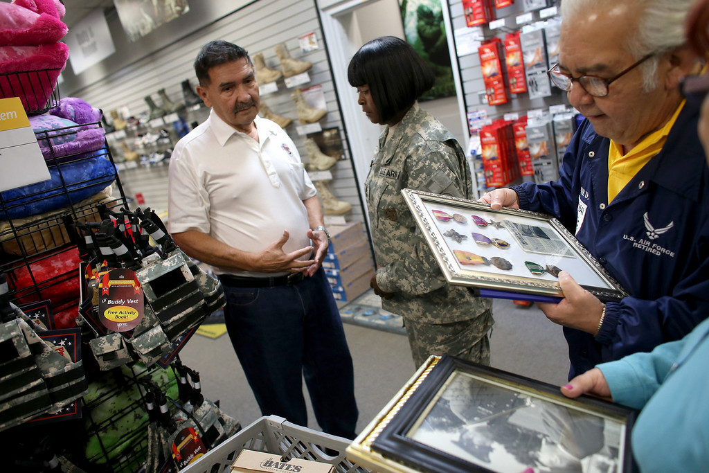 . U.S. Army Specialist Four Santiago J. Erevia speaks with Sgt. Kimberly Green as Jesse Dominguez (R) looks over the medals to be placed on his new military uniform to be worn during the Medal of Honor ceremony at the White House on March 18th for his actions while serving in the Vietnam war on March 11, 2014 in San Antonio, Texas.  (Photo by Joe Raedle/Getty Images)