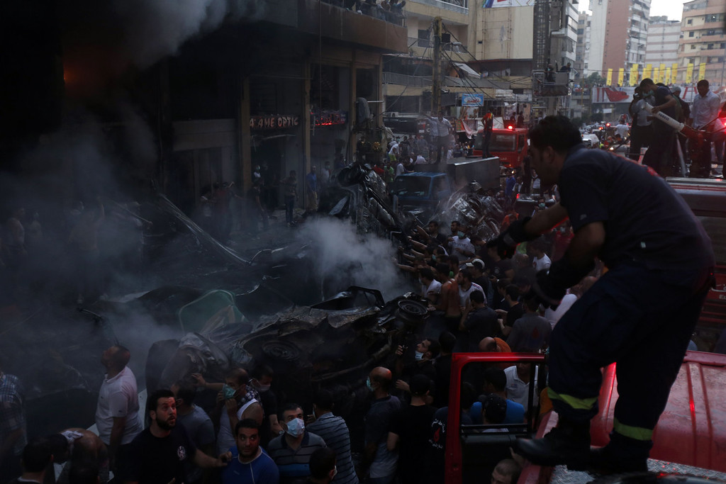 . Lebanese civilians and emergency personnel gather at the site of a car bomb between the Bir el-Abed and Roueiss neighborhoods, in the southern suburb of Beirut on August 15, 2013. A powerful car bomb killed at least six people and more than 100 wounded in a Beirut stronghold of Shiite movement Hezbollah, an army source and Lebanese Red Cross said. AFP PHOTO/STR-/AFP/Getty Images