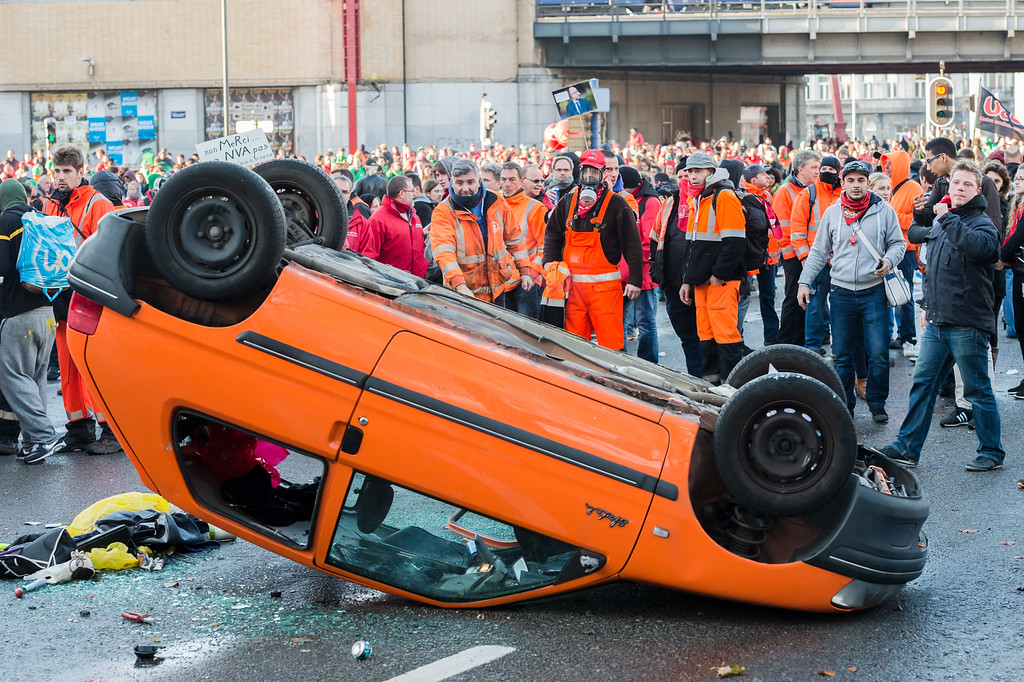 . Protestors stand behind a car they overturned during a national trade union demonstration in Brussels, Thursday Nov. 6, 2014. (AP Photo/Geert Vanden Wijngaert)
