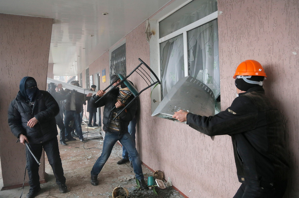 . Pro-Russian men storm a police station in the eastern Ukrainian town of Horlivka on Monday, April 14, 2014.  Several government buildings have fallen to mobs of Moscow loyalists in recent days as unrest spreads across the east of the country.  (AP Photo/Efrem Lukatsky)