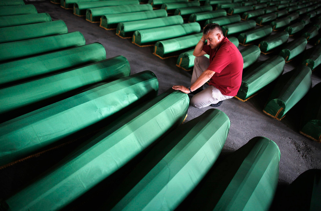 . A Bosnian man cries near the coffin of his relative, one of 409 newly identified victims of the 1995 Srebrenica massacre, in Memorial Center Potocari near Srebrenica July 10, 2013. The bodies of the recently identified victims will be transported to the memorial centre in Potocari where they will be buried on July 11 marking the 18th anniversary of the massacre in which Bosnian Serb forces commanded by Ratko Mladic killed up to 8,000 Muslim men and boys and buried them in mass graves. REUTERS/Dado Ruvic