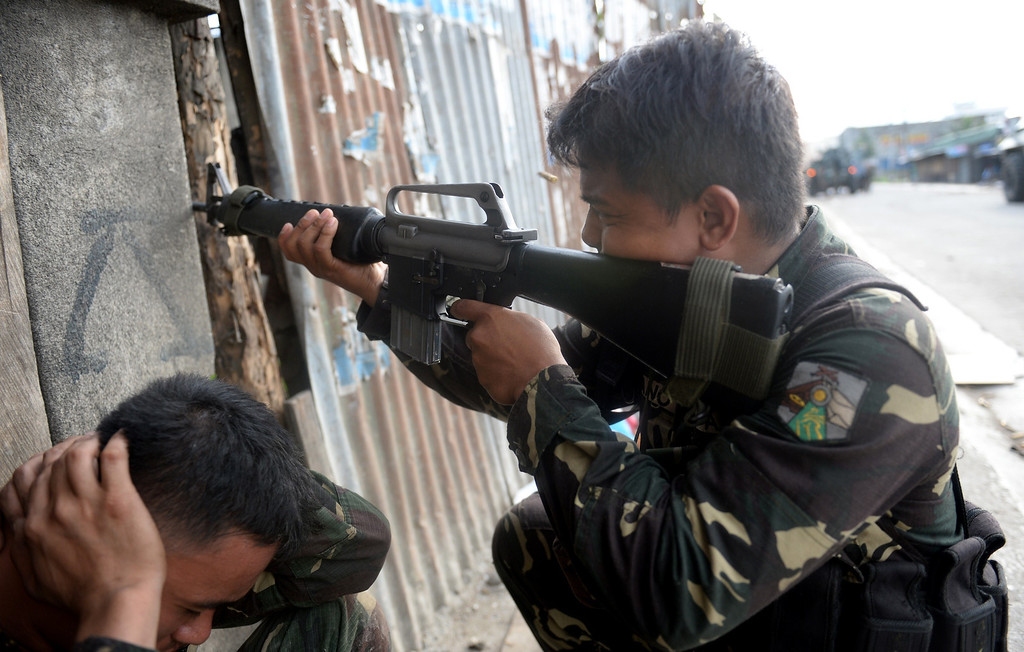 . A Philippine soldier fires his M-16 rifle at rebels\' snipers as another soldier covers his ears during a fire fight between government forces and Muslim rebels as stand-off entered its fourth day in Zamboanga City on the southern island of Mindanao on September 12, 2013.   AFP PHOTO/TED ALJIBE/AFP/Getty Images