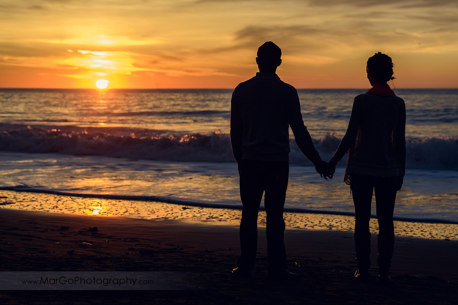 silhouette of man and woman holding hands and watching sunset over ocean during engagement session at San Francisco Baker Beach