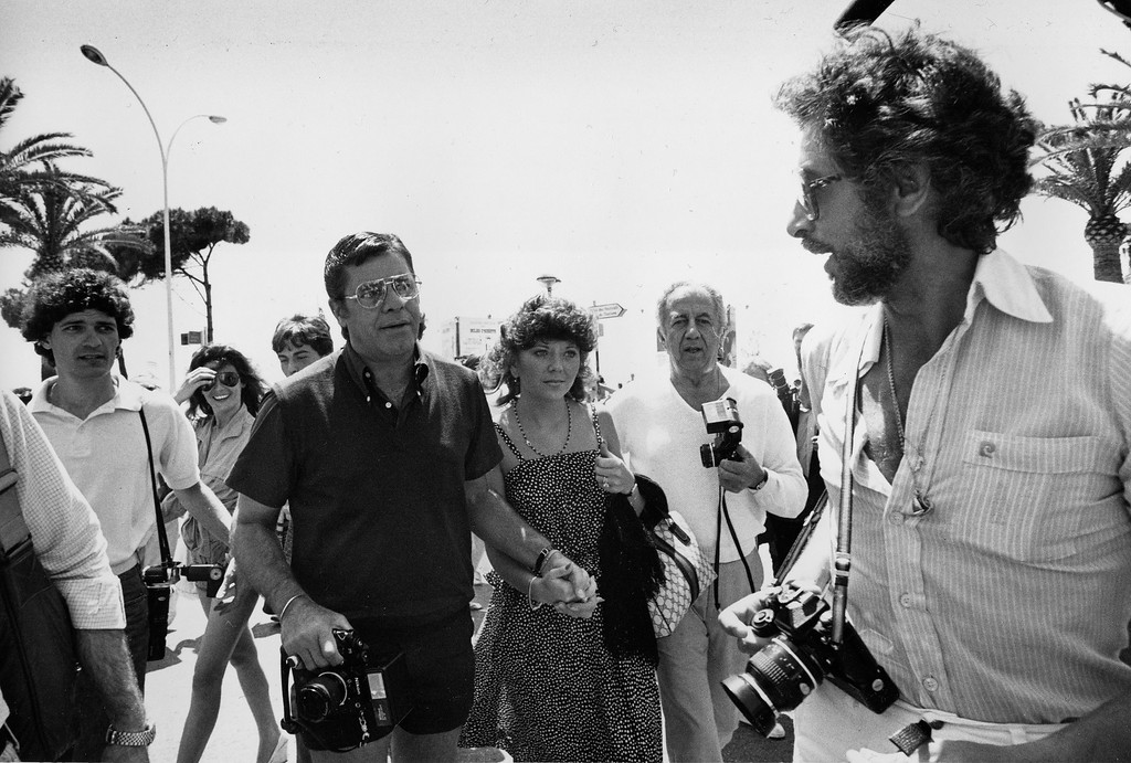 ". American actor Jerry Lewis, center, walks hand-in-hand with unidentified companion as he holds a camera in the other hand on the Croisette in the French Riviera, Cannes, France, May 24, 1982.  Lewis appears in the movie ""Bonjour Monsieur Lewis,\"" presented at the Festival.  (AP Photo/Levy)"