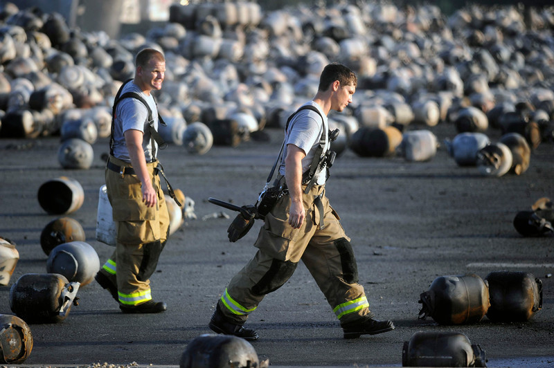 . Firefighters walk among thousands of exploded propane cylinders that litter the storage yard of a propane plant after massive explosions overnight in the plant\'s yard, in Tavares, Florida, July 30, 2013. Dozens of explosions rocked a propane tank servicing plant in central Florida, northwest of Orlando, late on Monday, injuring seven workers, at least three critically, and prompting the evacuation of nearby homes, authorities said.  REUTERS/David Manning
