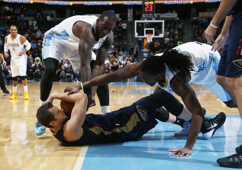 . New Orleans Pelicans center Jason Smith, front, cradles a loose ball as Denver Nuggets forwards J.J. Hickson, back left, and Kenneth Faried cover in the first quarter of an NBA basketball game in Denver on Sunday, Dec. 15, 2013. (AP Photo/David Zalubowski)