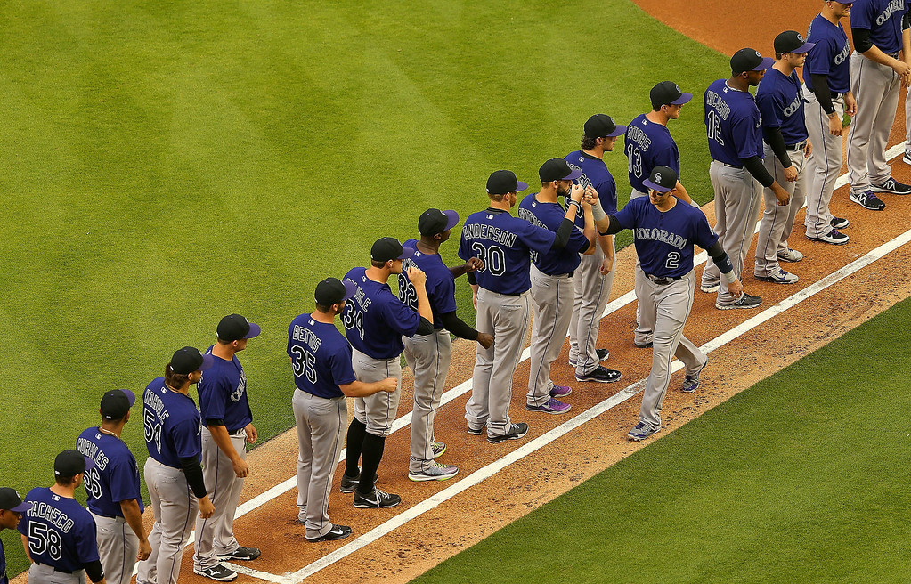 . Troy Tulowitzki #2 of the Colorado Rockies is greeted by teammates during Opening Day against the Miami Marlins at Marlins Park on March 31, 2014 in Miami, Florida.  (Photo by Mike Ehrmann/Getty Images)