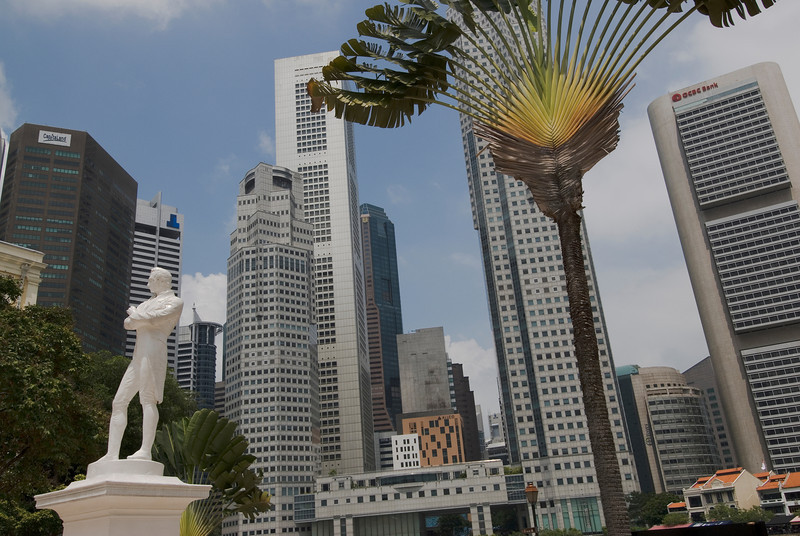 Wider shot of skyscrapers behind Stamford Raffles Statue in Singapore
